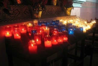 Votive candles in mission chapel. Photo by Anndelion.